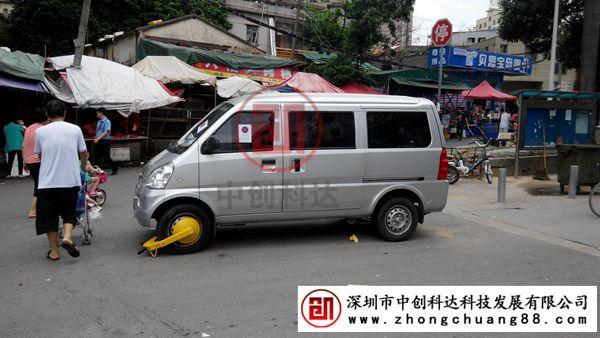 """在禁停标识下违停的面包车:被黄色车轮锁上锁了 深圳汽车数量排名前国第四名,如果每一位车主都不遵守车辆停放秩序并且不将车辆停放在规定的停车场内,那可想而知将是怎么样一个城市景观。面对这种情况,街道办执法工具中配置有一种执法神器""""车轮锁""""。 在龙华新区一街道办,小编就看到有一面包车在禁停标识下大胆的停放在那里,仔细瞧这附近是一生活商业区,周围大都是商店、市场,行人较多。这面包车违停之下,不但影响了其他车辆通行,还影响着行人出行安全。像这种违停车辆当然应该将车轮锁派上用场。 街道办工作"""